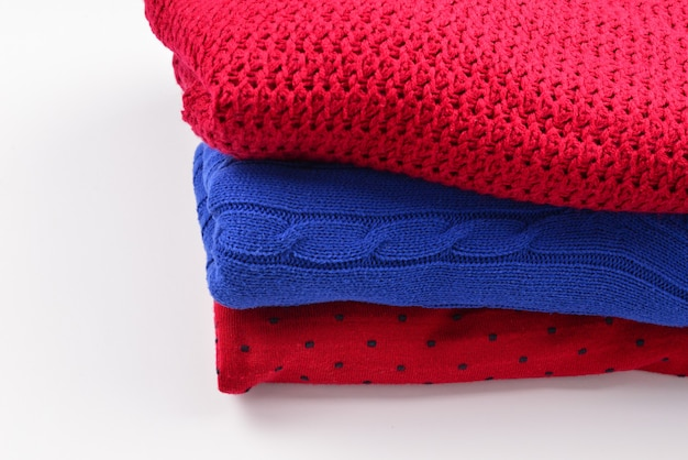 A stack of sweaters isolated on white