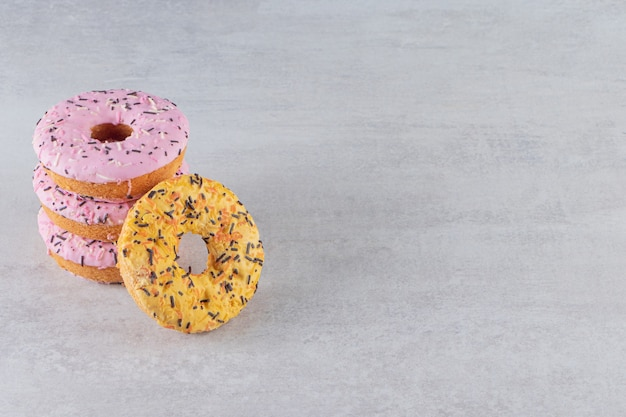 Stack of sweet donuts decorated with sprinkles on stone background.