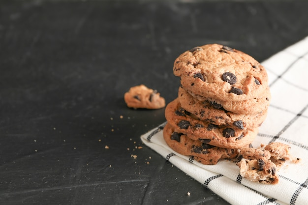 Stack of tasty chocolate chip cookies on napkin and wooden background. space for text