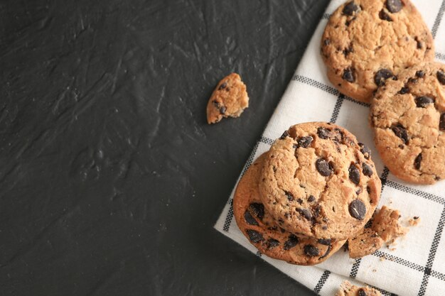 Stack of tasty chocolate chip cookies on napkin and wooden background, top view. space for text