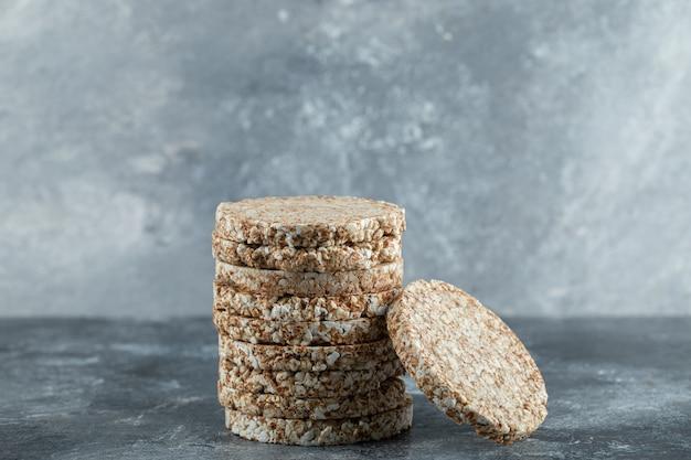 Stack of tasty crispbread on marble surface