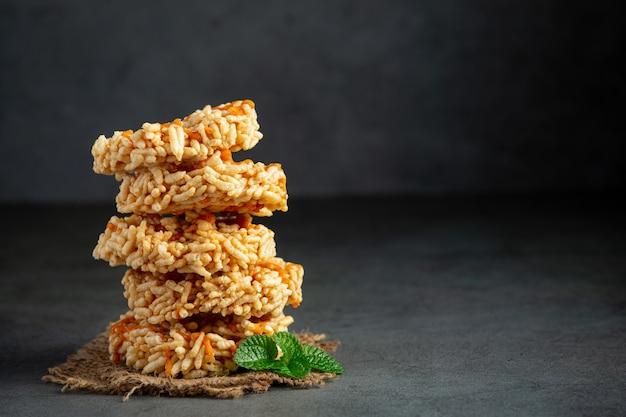 The stack of thai snack kao tan or rice cracker on dark floor