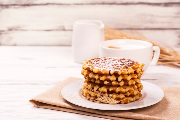 Stack of thick belgian waffles with sugar powder and cup of cappuccino coffee.