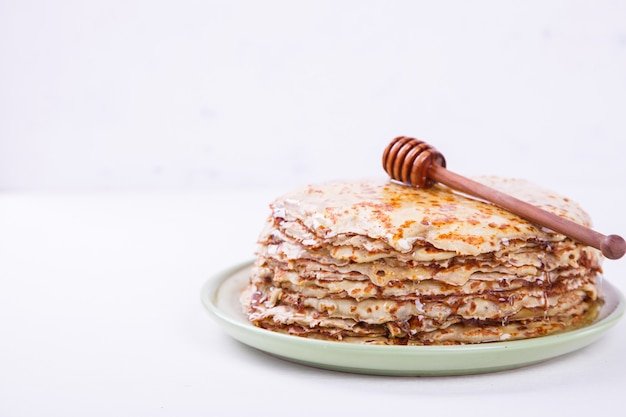 Stack of thin pancakes with honey