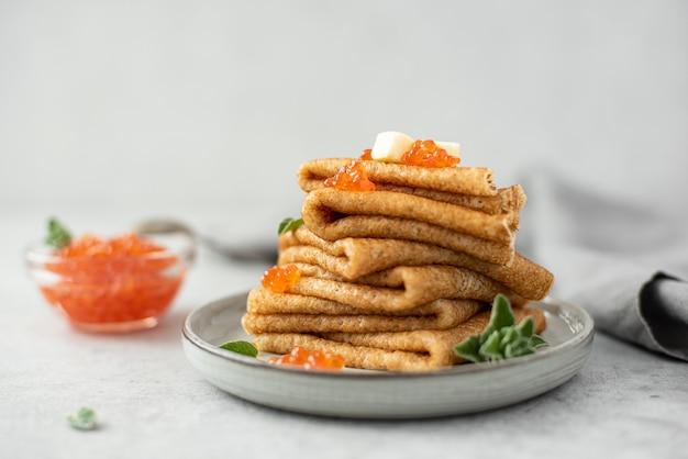 A stack of thin pancakes with red salted caviar and butter, close-up