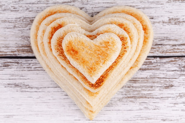 Stack of toasted bread hearts on wooden table, concept of support in big family