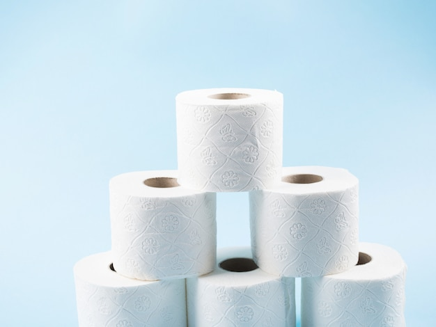 Stack of toilet paper rolls on blue backdrop