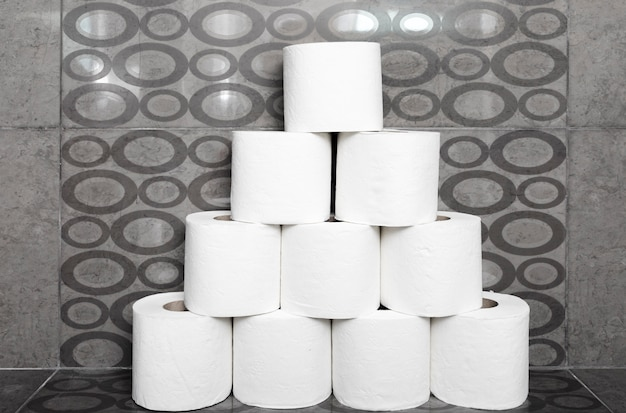 Stack of toilet paper rolls on shelf in bathroom