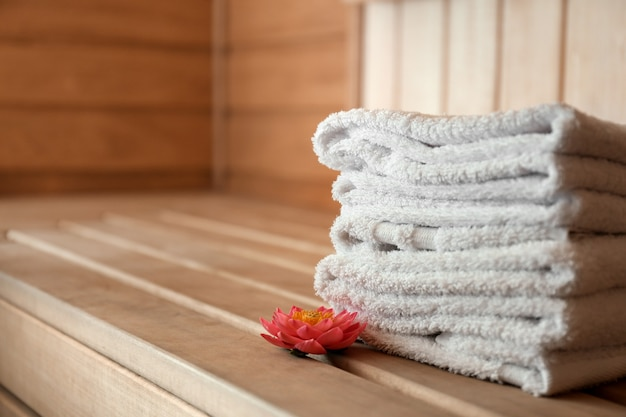 Stack of towels on wooden bench in sauna