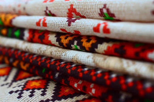 Stack of traditional ukrainian folk art knitted embroidery patterns on textile fabric