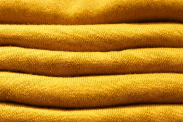 Stack of trend ceylon yellow woolen knitted sweaters close-up, texture, background