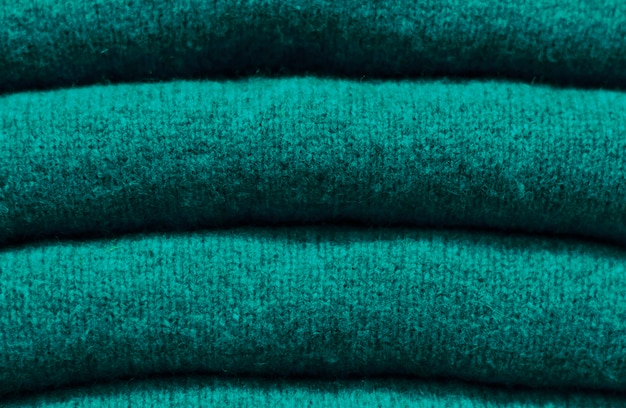 Stack of trend quetzal green woolen sweaters close-up