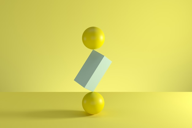 Stack of two yellow spheres and blue box in the middle  isolated on yellow background.