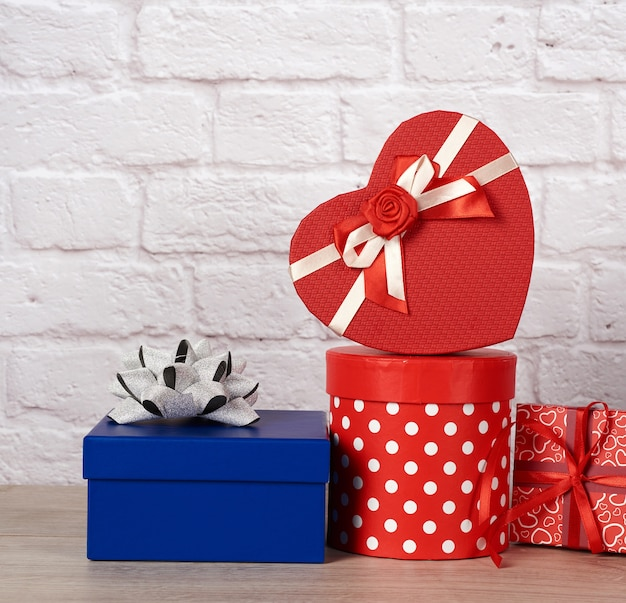 Stack of various boxes with gifts on white brick background