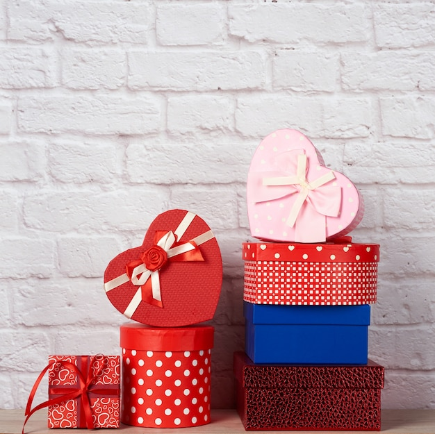 Stack of various boxes with gifts on white brick