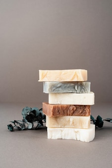 Stack of various handmade soap and eucalyptus on gray background, front view