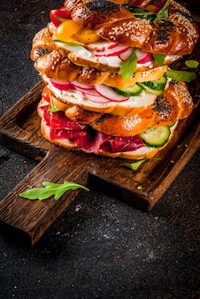 Stack of various homemade bagels sandwiches with sesame and poppy seeds, cream cheese,  ham, radish, arugula, cherry tomatoes, cucumbers, on cutting board. dark concrete surface