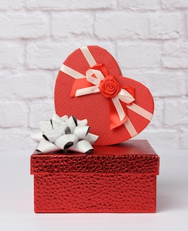 Stack of various red boxes with gifts on white background, festive backdrop