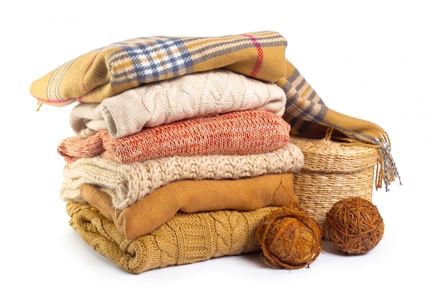 Stack of various sweaters isolated on white