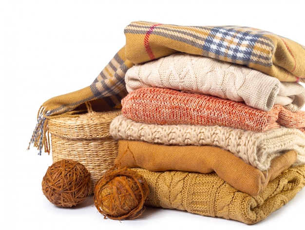 Stack of various sweaters isolated