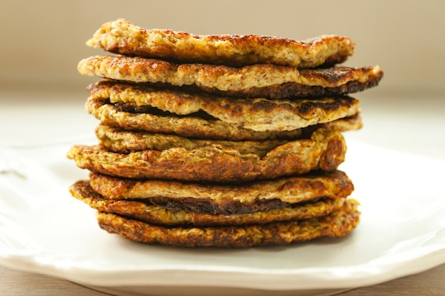 Stack of vegetable zucchini fritters served on white plate close up. healthy vegetarian vegetable fritters. top view. selective soft focus.
