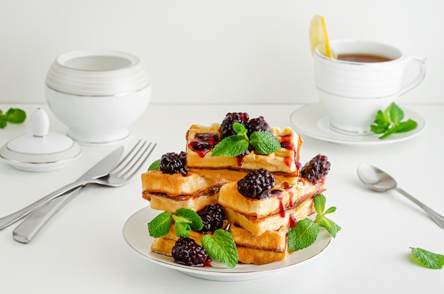 Stack of viennese waffles with blackberry jam and mint on white background