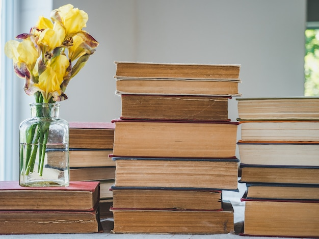 Stack of vintage books and beautiful flowers