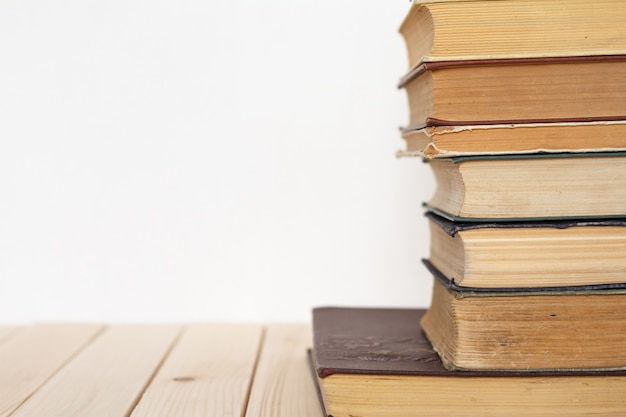 A stack of vintage books on a wooden surface against a white wall