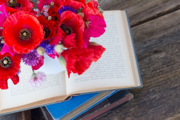 Stack of vintage old books  on table with field flowers
