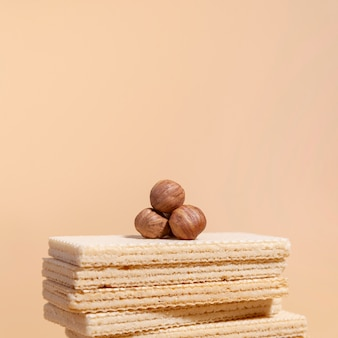 Stack of wafers with hazelnuts on top and copy space
