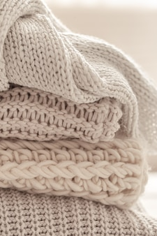 A stack of warm knitted items on blurred white background.