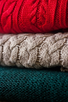 Stack of warm knitted sweaters close up.