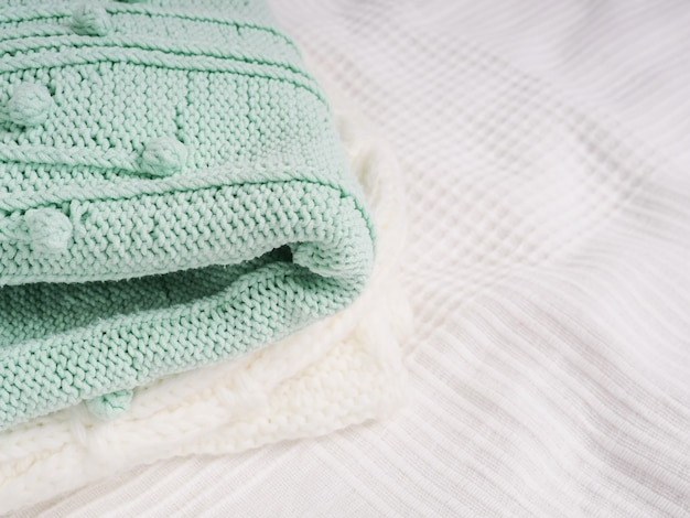 A stack of warm knitted things on a white bed. cozy clothes. household concept. folded knitted things white.