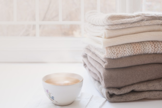 Stack of warm knitwears and cup of hot tea on windowsill on white window background.