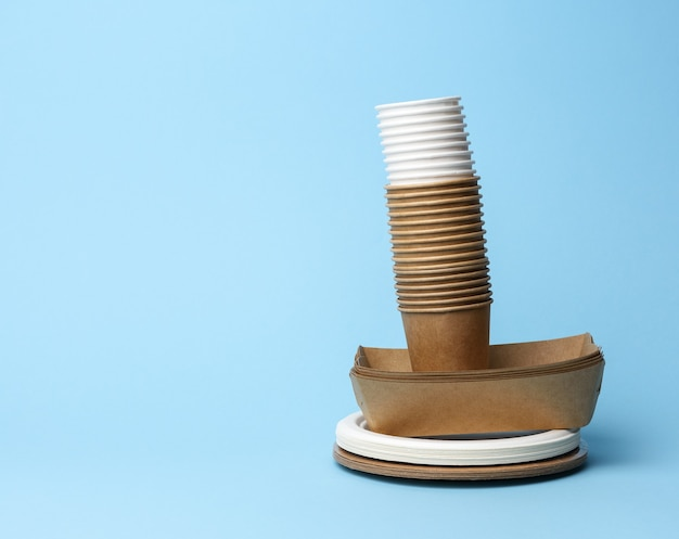 Stack of white and brown paper cups and round plates on a blue background, zero waste
