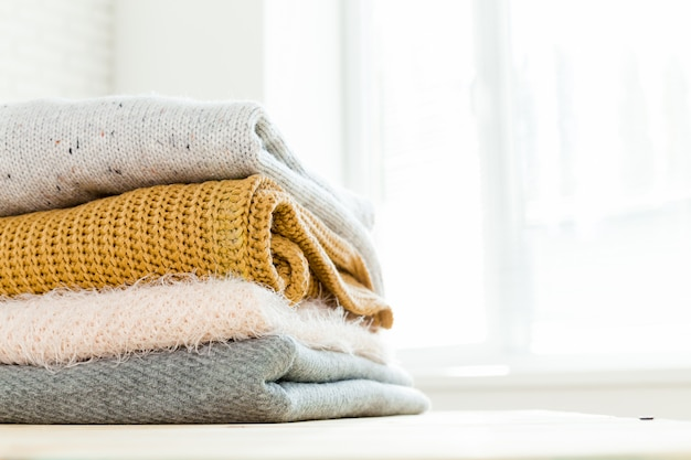 Stack of white cozy knitted sweaters
