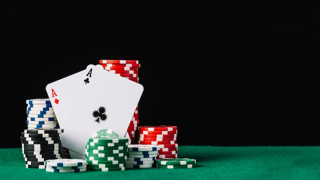 Stack of white; green; black and red casino chips with two aces on poker table