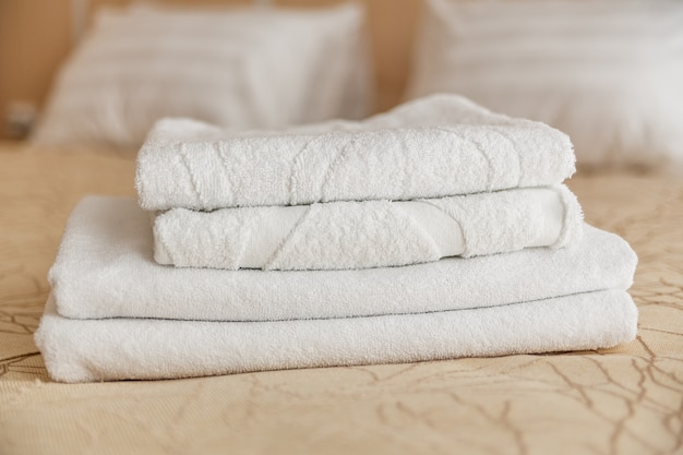 Stack of white hotel towel on bed in bedroom interior.