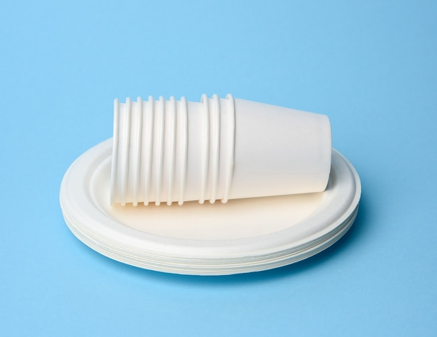 Stack of white paper cups and round plates on a blue background. plastic rejection concept, zero waste