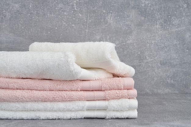 Stack of white and pink bath towels on gray. copy space