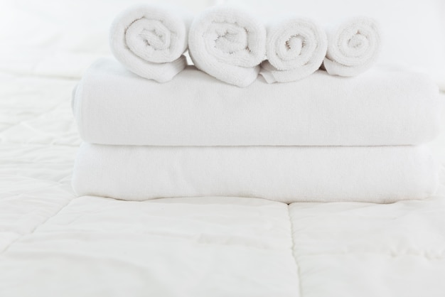 Stack of white towels on white bed in modern bedroom