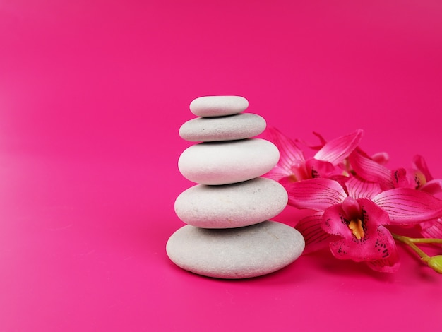 A stack of white zen stones on a pink background, minimalism.