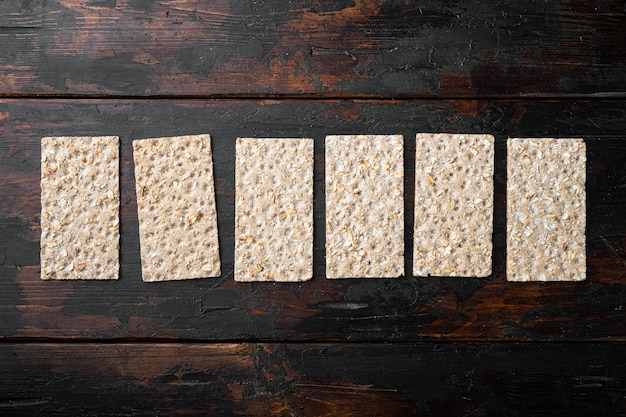 Stack of wholegrain crispy bread with sunflower, chia and sesames seeds set, on old dark wooden table, top view flat lay