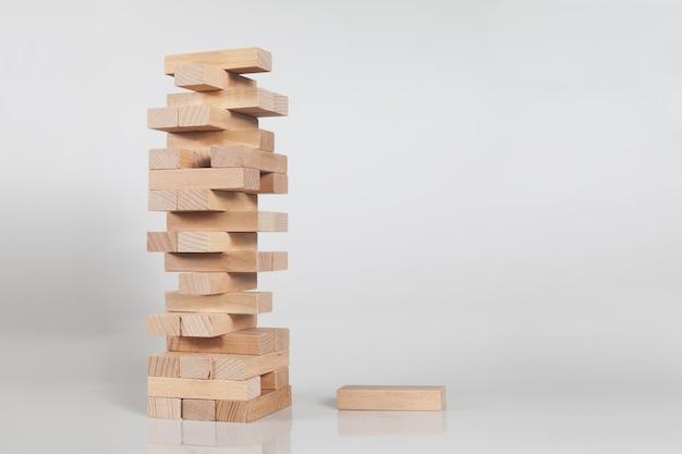Pila di una torre di blocchi di legno isolata su un muro bianco