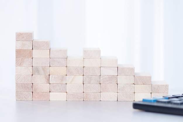 Stack of wooden blocks, calculator on whete sunlight background. step down, fall, recession, crisis concept.