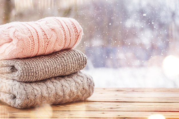 Stack of wool knitted clothes on wooden tableon winter background