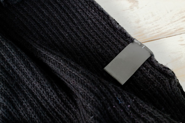 Stack of wool knitted warm sweater and white label for text
