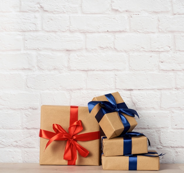 Stack of wrapped boxes in brown kraft paper and tied with silk ribbon
