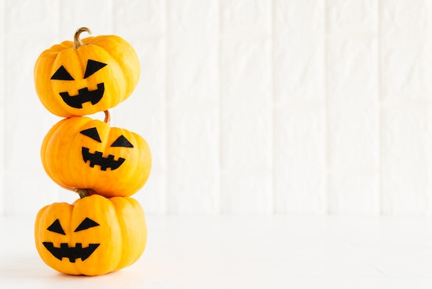 Stack of yellow ghost pumpkin on white brick block background