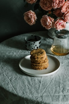 Stacked baked cookies on a plate near a cup and teapot, and pink roses in a vase on a table